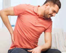 Photo of man in red polo sitting down, bending over from back pain.