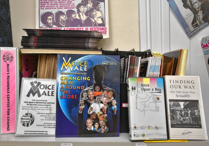 Magazines, books, and posters stacked against a wall with a Voice Male issue in the front.