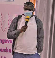 Man wearing a gray jacet and white shirt, speaking into a microphone while wearing a mask.