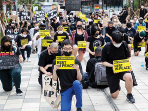 "Kneeling protesters hold signs that read ""May George Floyd rest in peace"" in Seoul, South Korea."