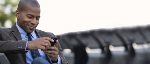 Black man wearing suit using smartphone outdoors
