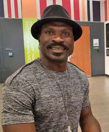A man with a moustache wearing a gray t-shirt and hat, smiling at the camera.