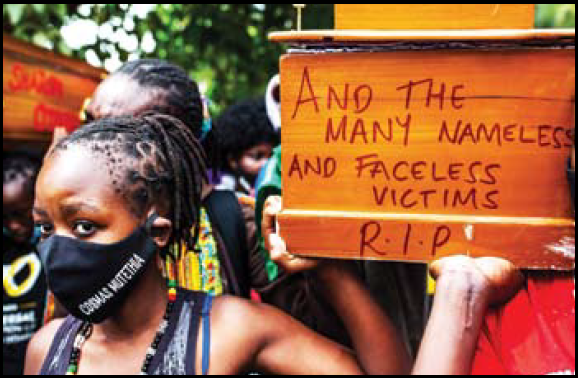 Cosmas Mutethia's wife wears a mask with the name of her husband, who was killed by Kenyan police during a night curfew, as she carries an empty coffin during a protest against police brutality in front of the parliament in Nairobi, Kenya.