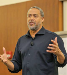 A man wearing a black shirt talking indoors.
