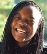 Headshot of a woman with braids, smiling.