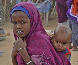 A girl wearing a magenta shawl carrying a baby on her back.