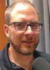 Headshot of a man with glasses and a short beard, wearing a gray collared shirt.