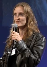 Photo of a woman with long borwn hair wearing a black leather jacket and speaking into a microphone