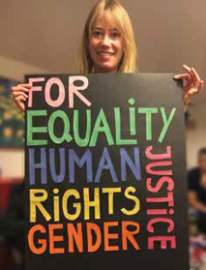 """Person holding up a black sign wich colored writing that reads """"For Equality, Human, Rights, Gender, Justice"""""""