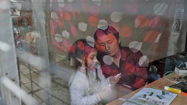 A father and daugher sitting at a desk working on a project using scissors and a glue stick.