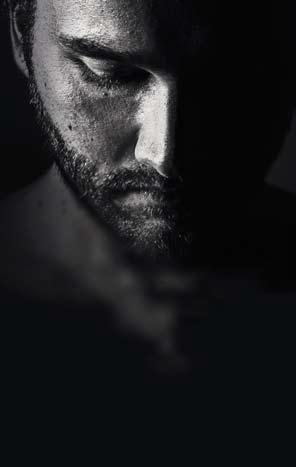 Greyscale silhouette.of a man's face looking down.