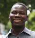 Headshot of a man outdoors wearing a gray collared shirt.