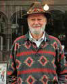 A bearded man standing outdoors wearing a patterned wool sweater and hat.