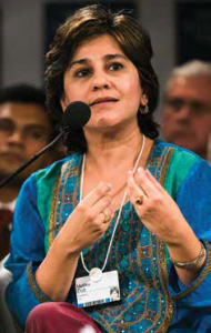 A woman speaking into a microphone while seated.