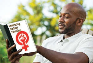 """Man wearing a white polo outdoors reading a book called """"Embracing Radical Feminism"""""""