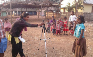 A woman adjusts a camera tripod in front of a young girl. A group of smaller children (and adults) stand nearby.