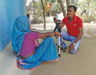 A man and woman sitting on the ground talking, with a camera tripod between them.