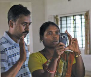 A woman holds up a camera she is practicing with as a man stands to her right, talking with her.