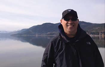 Man wearing a coat and cap standing in front of a lake