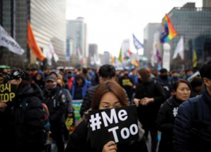 Person in a crowd holding a sign which says #MeToo
