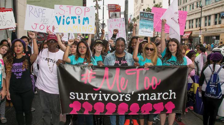 "March participants holding signs and a banner which reads ""#MeToo survivors march"""