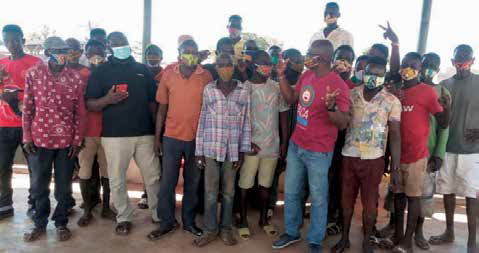 Group of about two dozen men wearing masks and standing together facing the camera.