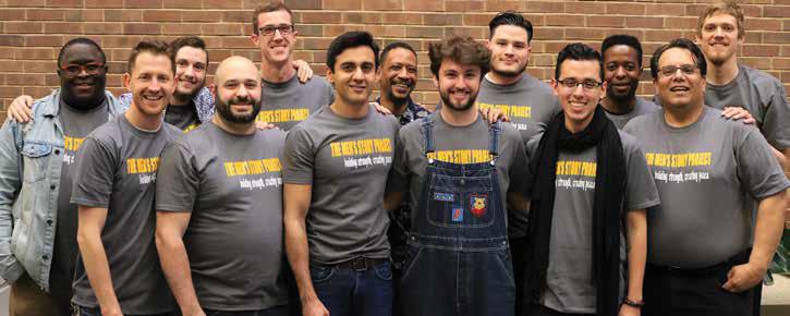 A dozen men men wearing identical gray t-shirts standing in front of a brick wall.