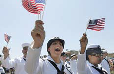 Sailors at a parade waving flags.
