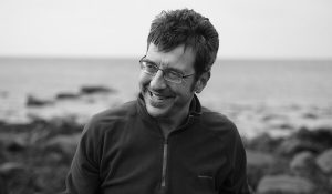 Black and white image of George Monbiot in front of water