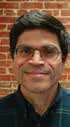 Headshot of man with glasses and dark hair, standing in front of a brick wall.