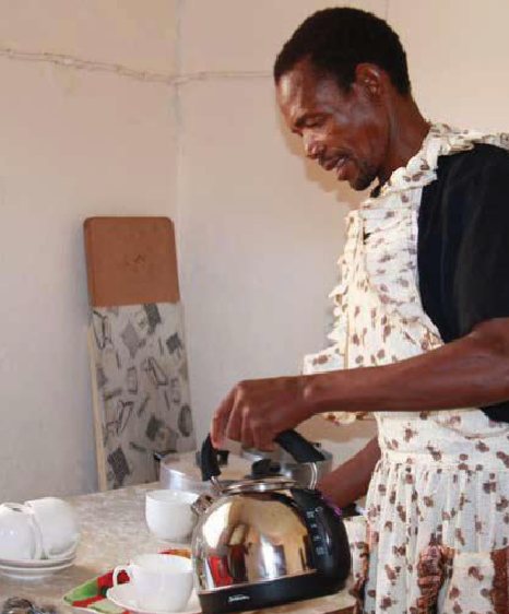 Man wearing an apron standing at a table and pouring tea.