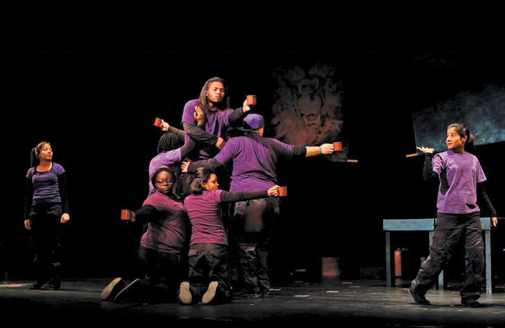 Seven people wearing purple shirts and black pants posed dramatically on a dark stage.