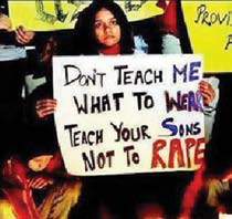 "Woman holding sign reading ""Don't teach me what to wear; Teach your sons not to rape."""