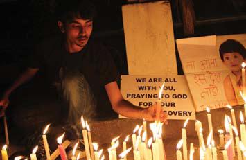 Person lighting candles at vigil.
