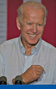 Photo of Joe Biden standing at a lectern and smiling.