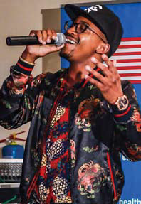 Black man speaking into a microphone at an event.