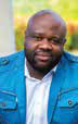 Headshot of a man wearing a white shirt and light blue blazer.