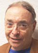 Headshot of a man with short hair and glasses, wearing a brown suit.