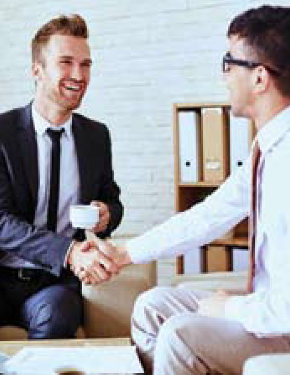 Two mean wearing formalwear, seated and shaking hands. One is holding a coffee cup.