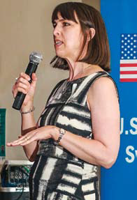 White woman with shoulder-length brown hair speaking into a microphone at an event.