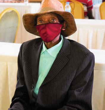 Man wearing a suit, hat, and red mask sitting at a table and listening.