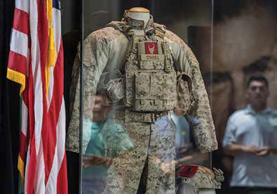 Uniform belonging to Navy SEAL Robert O'Neill on public display behind a glass case.