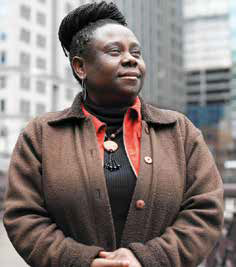 A woman with short hair wearing a brown sweater, standing in front of an office building.