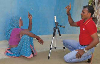 A man and woman sitting on the ground talking, with a camera tripod between them. They are both pointing up.