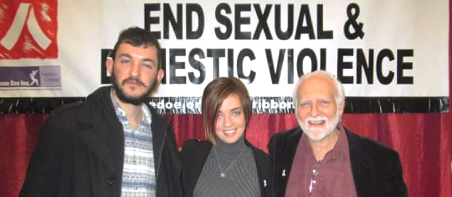 Amanda Pickett, Tom Gardener, and Rob Okun facing he camera in front of a red curtain beneath white banner reading End Sexual and Domestic Violence