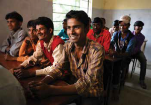 A group of young men sit smiling at three rows of desks, watching a presenter off-screen.