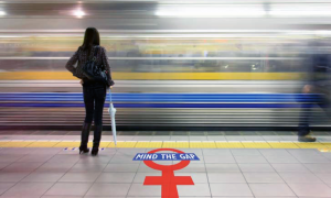 "Woman standing on a subway platform. ""Mind the Gap"" and the symbol for female are painted on the platform floor.."