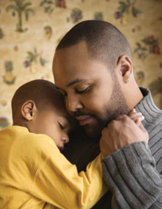 father wearing sweater holding young son