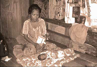 Grayscale photo of Cambodian woman and baby. THe woman is sitting on the ground and the babie is lying down.