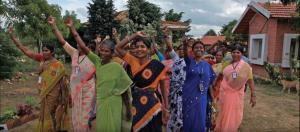 group of women outside raising hands